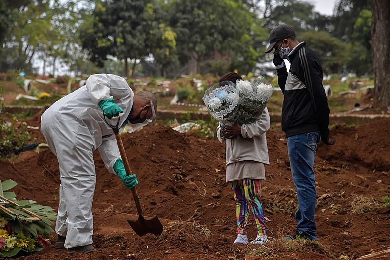 An employee digs next to relatives of a person who died from COVID-19 at the Vila Formosa cemetery, in the outskirts of Sao Paulo, Brazil on May 20, 2020. – Brazil has emerged as the latest flashpoint in the coronavirus pandemic. The country has registered more than 270,000 cases and nearly 18,000 deaths so far, and the increase in infections is not expected to peak until June. (Photo by NELSON ALMEIDA / AFP)