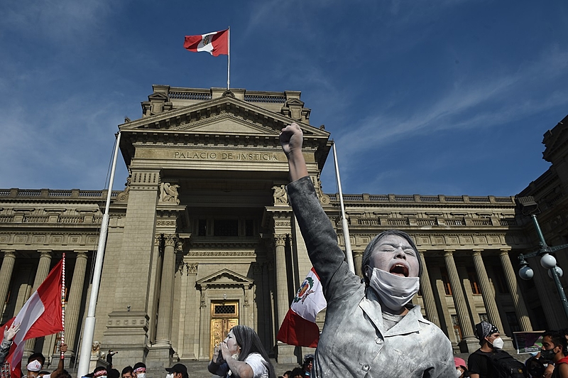 A supporter of Peruvian ousted President Martin Vizcarra raises her fist as she shouts slogans during a protest against the government of interim president Manuel Merino outside the Palace of Justice in Lima on November 14, 2020. – Speaker of Congress Manuel Merino assumed office on November 10 as Peru's third president in four years, amid street protests and market jitters after the impeachment of Martin Vizcarra over corruption allegations. (Photo by ERNESTO BENAVIDES / AFP)