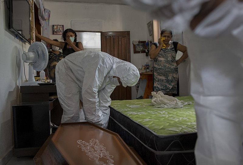 Relatives react as municipal workers from SOS Funeral remove the body of 75-year-old Adamor Mendonca Maciel from his home in Manaus, in the Brazilian state of Amazonas, on January 16, 2021 after he died of COVID-19. (Photo by MICHAEL DANTAS / AFP)