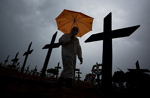 A worker wearing a protective suit and carrying an umbrella walks past the graves of COVID-19 victims at the Nossa Senhora Aparecida cemetery, in Manaus, Brazil, on February 25, 2021. – Brazil surpassed 250,000 deaths due to COVID-19. (Photo by MICHAEL DANTAS / AFP)