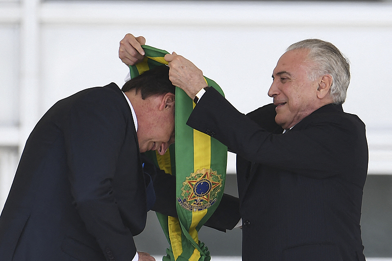 Outgoing Brazilian president Michel Temer (R) hands over the presidential sash to Brazil's new president Jair Bolsonaro at Planalto Palace in Brasilia on January 1, 2019. – Bolsonaro takes office with promises to radically change the path taken by Latin America's biggest country by trashing decades of centre-left policies. (Photo by EVARISTO SA / AFP)